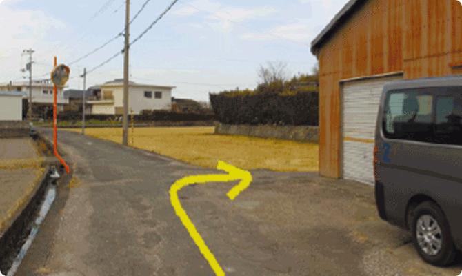 右手にシャッター扉の倉庫を見ながら右折。狭い道なので、車での右折が厳しい場合はこの倉庫の前に駐車して下さい。